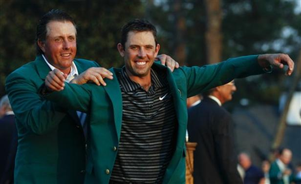 Former champion Phil Mickelson, back, helps Charl Schwartzel of South Africa with his green Masters jacket after winning the Masters  golf tournament Sunday. AP Photo by Charlie Riedel