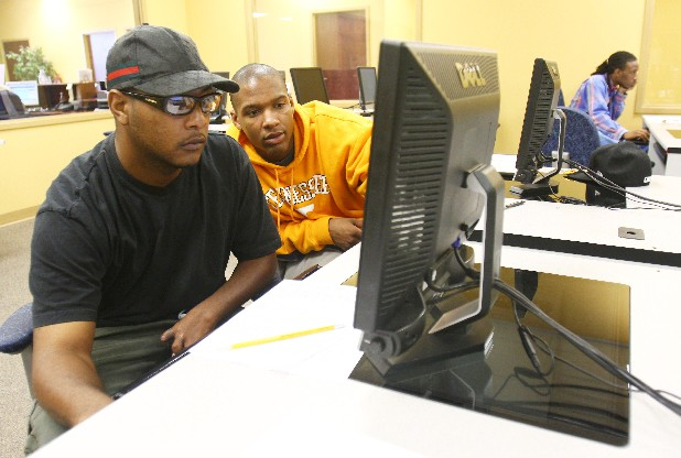 Timothy Goines, left, has help from Adrian Craighead while looking for jobs on the computer at the Tennessee Employment Service Office at Eastgate Center in Brainerd in this file photo.
