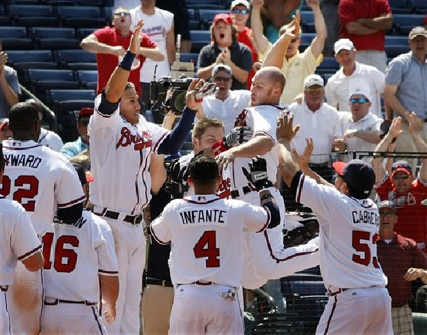 Atlanta Braves' Brooks Conrad, second from right, leaps at home plate as he is congratulated by teammates after hitting a walk-off grand slam to beat the Cincinnati Reds 10-9 in a baseball game in Atlanta on Thursday, May 20, 2010. (AP Photo/The Atlanta Journal & Constitution, Curtis Compton)