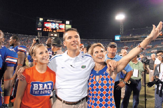 Florida coach Urban Meyer and his wife Shelley Meyer, right and daughter Gigi Meyer, left, celebrate after the Gators beat Georgia in Jacksonville, Fla. Meyer is stepping down as coach after the Gators appearance in the Outback Bowl. (AP File Photo/Stephen Morton, File)