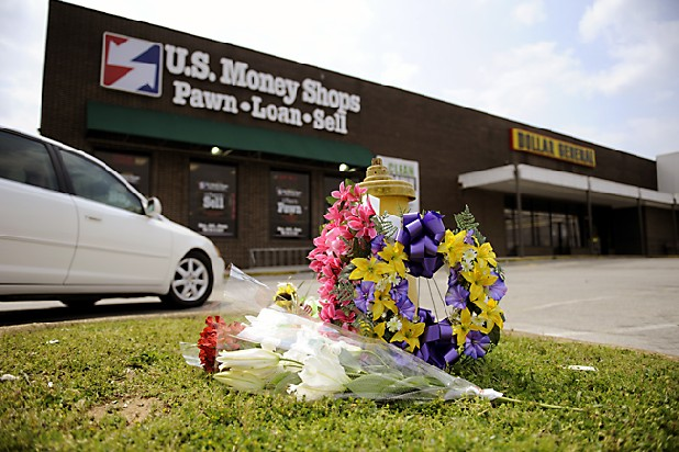 A car drives by a small group of flowers placed in front of U.S. Money Shops in Brainerd where police Sgt. James Timothy Chapin was killed Saturday after responding to an armed robbery.