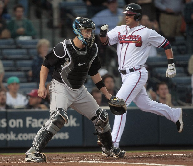 Atlanta Braves' Martin Prado (14) scores on a Nate McLouth double as Florida Marlins catcher John Buck (14) waits for the throw in the third inning of a baseball game Tuesday, April 12, 2011, in Atlanta. (AP Photo/John Bazemore)