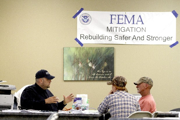 FEMA mitigation specialist Pedro Gazmey, left, talks with Windy Bond, center, and her fiance Wayne Sorrels on Saturday at the disaster center on the campus of Southern Adventist University in Collegedale.
