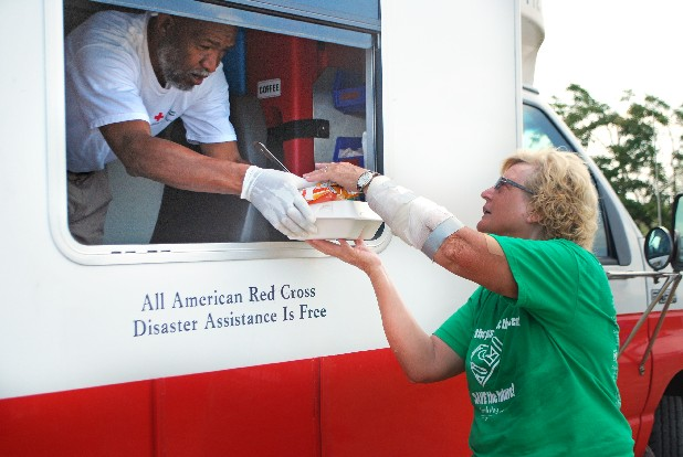 A Red Cross volunteer hands a hot meal to Kathleen Anderson. The Andersons' Jackson County, Ala., home was destroyed on April 27 and they are living in a travel trailer while they clean up debris. 