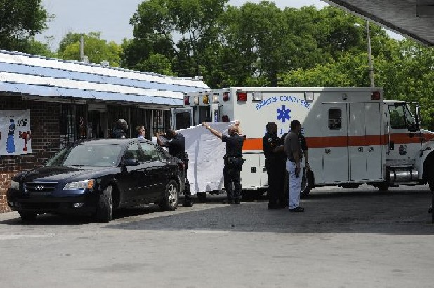 Police men hold up a sheet as they transport the body of a 53-year-old man from Big K Convenience store at 909 Dodson Ave. to the ambulance Thursday afternoon in Chattanooga, Tenn. The victim was shot in the head after he went inside the store Thursday morning.