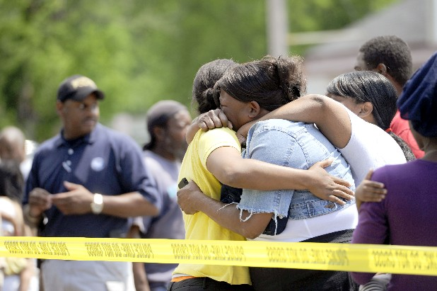 Family members and friends of 53-year-old shooting victim Herbert Strickland huddle together as they watch police officers transport the body to the ambulance Thursday in Chattanooga. The man was shot in the head at the Big K Convenience store at 909 Dodson Ave.
