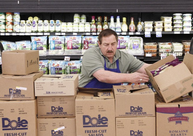Produce manager Ralph Dockery restocks bagged salads in the produce department at the Food Lion in Rocky Face, Ga. Area Food Lion grocery stores are attempting to bring more customers in by revamping their stores with fresher produce, wider aisles, new branding, better lighting and faster checkout lanes. 