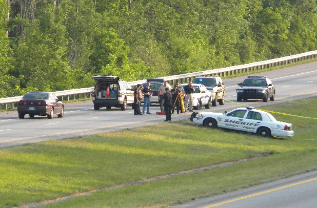 Investigators search for clues in the median of I-75 Saturday where a Bradley County deputy sheriff stopped to check on a woman and two small children walking. The woman allegedly slashed the deputy with a knife, and he fired at her as she stole the patrol car. The woman drove a short distrance before plowing through a fence and coming to rest on a Cleveland street.