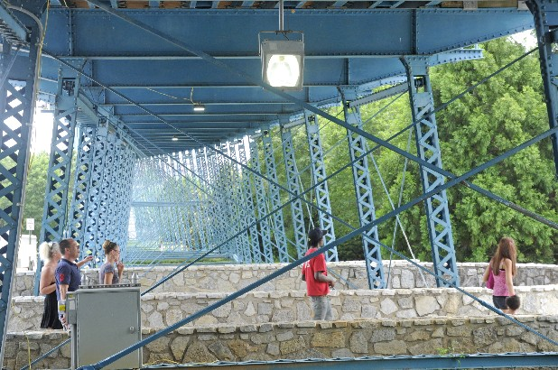 Visitors to Coolidge Park walk below the Walnut Street Bridge Monday with new lights illuminating the area underneath the bridge.