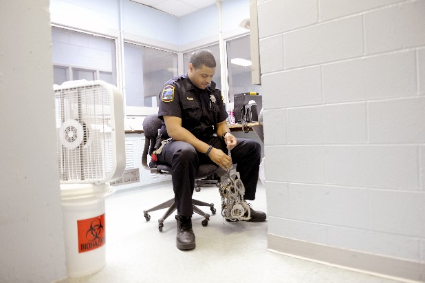 Micah Wilkerson sits in front of a fan inside of the Hamilton County Sheriff's Office in Chattanooga in order to cool down from the rising temperatures inside the building while the motor for the air conditioner awaits repairs.  In order to accommodate the heat, the inmates were permitted to wear their jumpsuits to their waists and were given Popsicles.