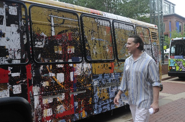 Rodney Simmons looks Thursday at one of three newly covered shuttle buses on display at Miller Plaza during River City's 25th anniversary celebration. Designs by artists were used to decorate five buses.