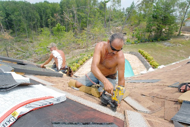 Brian Cabrera, right, and William Howard work to put a new roof on a tornado-damaged home in southern Bradley County. They and other local contractors have seen a large boost in business in the wake of recent widespread local storm damage.