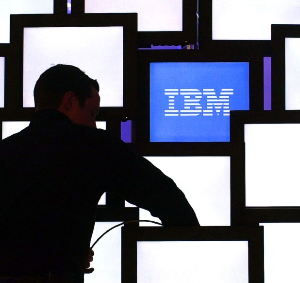 A worker installs monitors at the IBM booth in a file photo from the Cebit fair in Hanover, northern Germany. IBM was formed on June 16, 1911, as the Computing Tabulating Recording Co. in a merger of four separate companies. The new business with a plant in Endicott, N.Y., made scales, time clocks, cheese slicers and — significantly for its future — machines that read data stored on punch cards. (AP Photo/Fabian Bimmer)