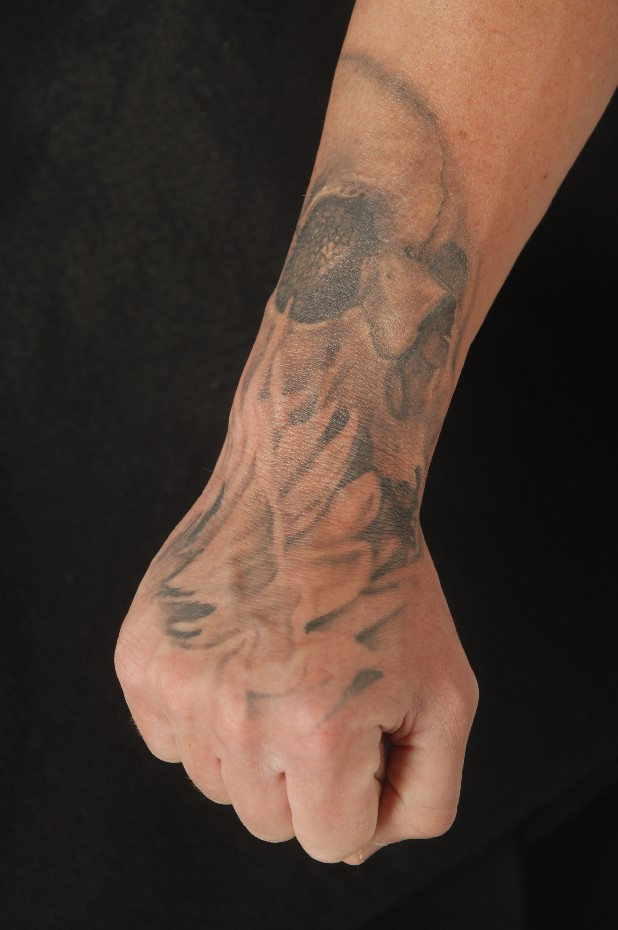"Brent Humphries shows a tattoo on his wrist and hand that he wears in honor of his wife. The daisy is her favorite flower and the skull represents the concept of ""Until death do us part."""
