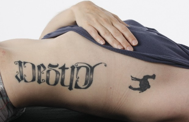"Jenny Holcomb displays her tattoos that memorialize her father. The tattoo on the left spells both ""destiny"" and ""choice""."