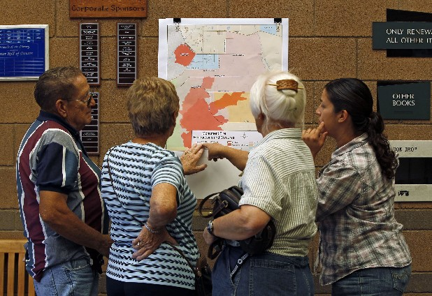 Residents look at the latest evacuation map at the public library in Sierra Vista, Ariz. About 10,000 people remained evacuated on the outskirts of Sierra Vista about 15 miles north of the border where the so-called Monument Fire swept off a mountain and destroyed 14 homes and four businesses Sunday.