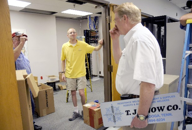 Tom Snow, right, CEO of T.J. Snow Co., talks with Bill Cooper of Crime Prevention Resources about installing protection systems at the new Airport Road location. Sam Snow, center, listens to the exchange.
