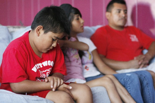 Cristian Valladares, from left, looks down as he, Jenifer Valladares and Leslie Valladares listen in Dalton, Ga,. as their father, Erick Munoz, speaks about their mother's deportation. The children are being sent to live with their mother in Mexico.