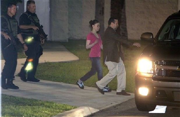 Casey Anthony, center, walks to a SUV with her lawyer Jose Baez after her release from the Orange County Jail in Orlando, Fla., early Sunday, July 17, 2011. Anthony was acquitted July 5 of murder in the death of her daughter, Caylee. (AP Photo/John Raoux)
