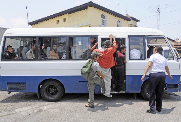 Guatemalan nationals, who just arrived in Guatemala City on a U.S.-chartered flight for deportees from Arizona, board minibuses provided by the Guatemalan government to drive them to bus stations so they can return to their villages.