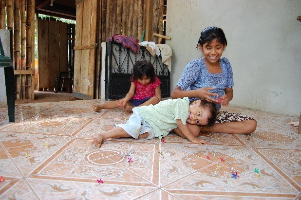 Heidi Sales Morales, 10, plays a game of Jacks with her sister Roselia Sales Morales, 2, and Sofia Sales Morales, 4, in the back, outside their home in the village of el Xab in Retalhuleu, Guatemala. Their mother, Angela Surama Morales lived in Chattanooga for about five years until she got detained in an immigration raid at Pilgrim's Pride in 2008 and their father left to work in the United States almost 10 years ago.