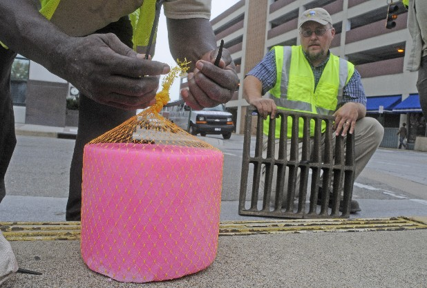 City workers place deodorizing tablets into downtown grates.