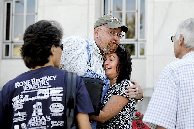 Phillip Marramore  embraces Kelle Chapin, the wife of Sgt. Tim Chapin, while Lisa Roberson, Tim's sister, and Ralph Chapin, Tim's father, watch Wednesday outside the U.S. District Courthouse after Rachel Mathews and her boyfriend James Poteete pleaded guilty to three of 10 charges of aiding Jesse Mathews, who shot and killed Chapin on April 2 on Brainerd Road.