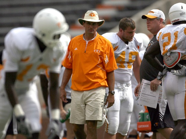 Tennessee head coach Derek Dooley looks on while wide receivers run a drill during a warmup session prior to a team scrimmage Saturday at Neyland Stadium.