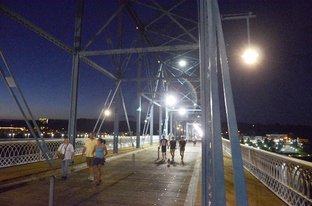 People walk across the Walnut Street Bridge on Sunday. The brighter area behind the walkers is a test of new emergency lights for the downtown Chattanooga pedestrian bridge.