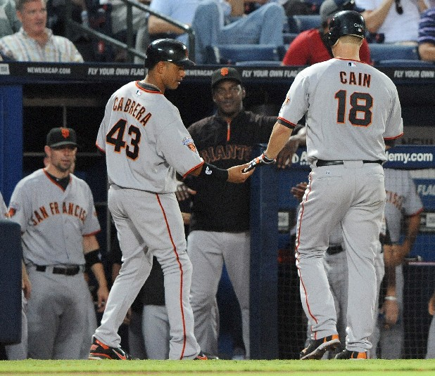 San Francisco Giants pitcher Matt Cain, right, is greet at the dugout by teammate Orlando Cabrera after driving in a run with a sacrifice fly ball against the Atlanta Braves in the fourth inning of a baseball game on Wednesday, Aug. 17, 2011, at Turner Field in Atlanta. (AP Photo/Erik S. Lesser)