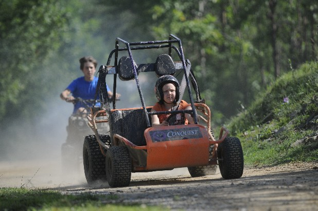Faith Guelde rides her go cart with brother, Kaleb Guelde, at their Hinkle home.