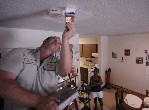 David Moore, near left, patches a ceiling in Brenda Robinson's apartment at Cromwell Hills Apartments.