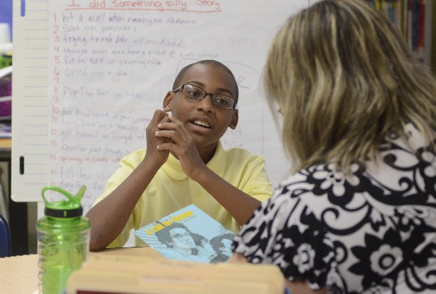 East Lake Elementary fourth-grader Tiryq Thomas takes a sixth-grade level reading test with teacher Felicia Banks on Monday. He is one of 12 Hamilton County students to score a perfect 900 on the math portion of the TCAP, the state's standardized test.