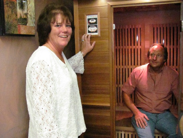 Lisa Nelson of Endless Escape Tanning & Health Spa in Dayton, Tenn., explains how to use far infrared medical saunas. Fiance and co-owner Lonnie Rogers sits inside.