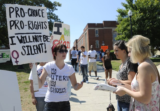 Kristian Kastner, left, holds a sign as Mariah Pike, center, and Malaina Horn sign a petition Tuesday against a display of abortion images placed at the University of Tennessee at Chattanooga.