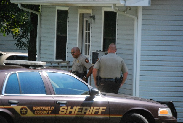 "Investigators gather evidence at Julius ""Wayne"" Smith's  house on Honeybee Way in Rocky Face, Ga. Smith and a teenage girl were shot to death and his house set ablaze Saturday."