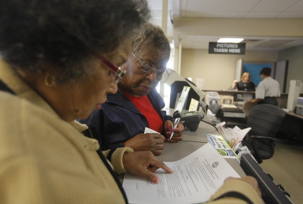 Dorothy Melvin, center, gets help from Charline Kilpatrick as she fills out a form to get a new license with her photo on it. Dorothy and Joshua Melvin added photos to their driver's licenses at the Driver Services Center on Monday afternoon as part of the state's new law that requires a photo ID to vote.