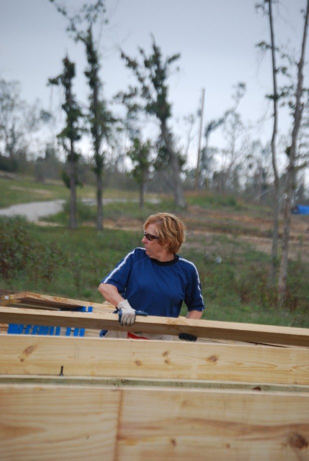 Coleen Pridemore carries a board for the frame of a cabin at Sand Mountain Bible Camp in Trenton, Ga. The cabins will serve as boy's dorms when they are completed. An April tornado caused about $2.3 million worth of damage to the camp.