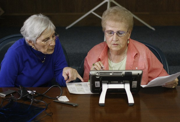 Orma Luckey, left, and Marie Holder, right, test out the new Expresspoll, which contains the names of all registered voters in the city. These machines will be used in Lafayette, Ga. in the up coming election.  The upcoming election will be the first time Lafayette, Ga. uses electronic machines to facilitate voting.