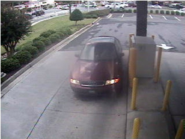 Surveillance photo of a burgundy or red Audi, bearing a distinctive black designer-type tag on the front, taken at the drive through ATM at Walnut Avenue and Tibbs Road in Dalton, Ga. The driver of the vehicle is suspected of being involved in the placement of a card skimmer device at the Regions Bank ATM.