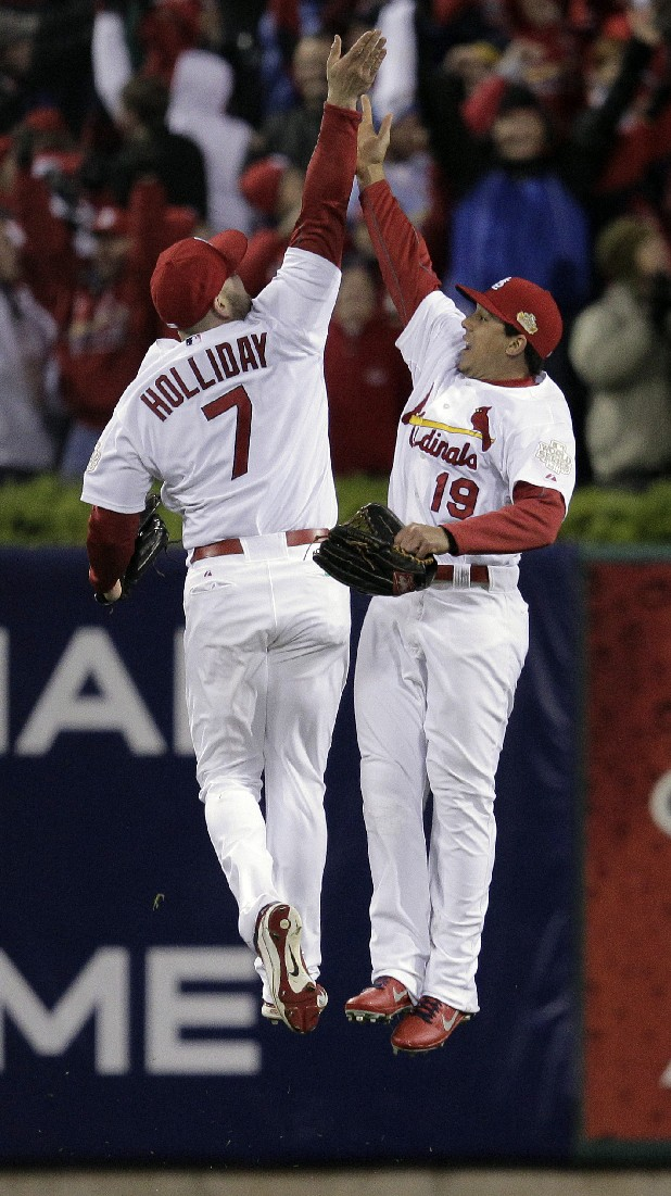 St. Louis Cardinals' Matt Holliday (7) and Jon Jay (19) celebrate after the final out in the ninth inning of Game 1 of baseball's World Series against the Texas Rangers Wednesday, Oct. 19, 2011, in St. Louis. The Cardinals won 3-2 to take a 1-0 lead in the series. (AP Photo/Charlie Riedel)