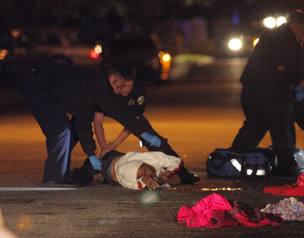 First responders help a shooting victim roll onto her back Friday night. Three people were shot at the corner of Fifth Avenue and East 31st Street. Chattanooga police arrested six juveniles and an 18-year-old in connection with the attack.