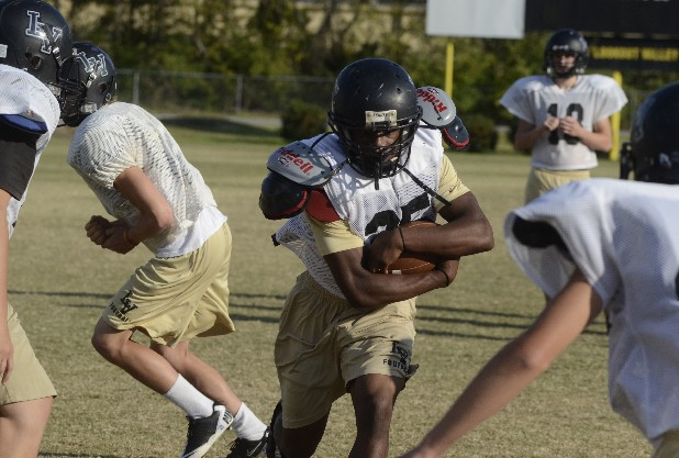 Lookout Valley High School running back Jamal Jones, center, carries the ball in practice at the school Monday.