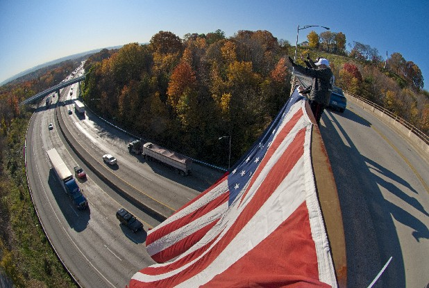 Standing atop Crest Road in Chattanooga, Tenn., Viet Nam  military veterans Robert Bunch, Ron Tatum and Ron Harvey wave to motorists along I-24 Friday in celebration of Veterans Day.