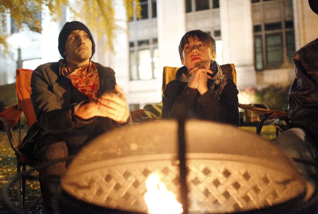 Chris Artell, left, and Quint Hawn warm themselves next to a fire at Occupy Chattanooga on Thursday night. Artell says he has been present at Occupy Chattanooga since the first general assembly but Thursday was 11-year-old Quint's first night visiting the encampment.