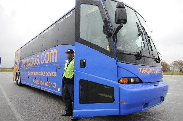 Freddie Taylor stands at the door of the Megabus, a busing service that stops at several locations with fares starting at $1. The bus stops in Chattanooga at the parking lot of the Rave Theater.