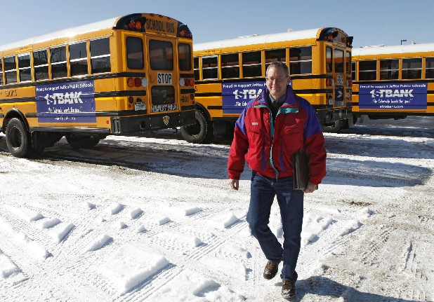 Marc Horner, fleet manager for Jefferson County Public Schools, walks near buses with advertisements on their sides at the school's maintenance facility in Lakewood, Colo. Some school leaders in Georgia want to follow Colorado's lead and allow businesses to buy advertising space on school property.