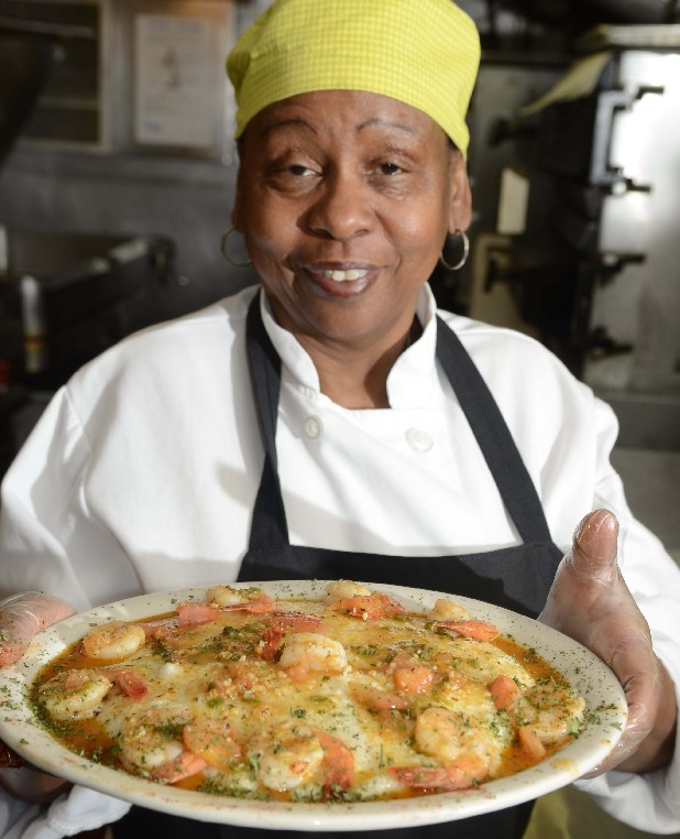 Joyce Ballard, executive chef on the Delta Queen, holds the finished plate after demonstrating how to make her recipe for shrimp and grits. The dish is one of the items that will be on the menu for Thanksgiving at the restaurant, located onboard the historic paddlewheel docked on the Tennessee River at Coolidge Park in downtown Chattanooga.