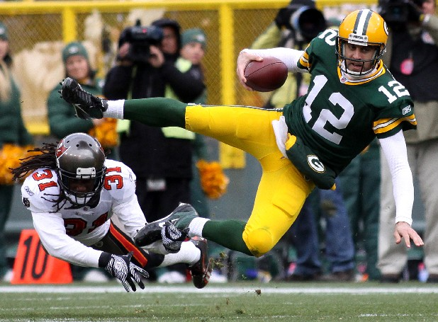 Green Bay Packers quarterback Aaron Rodgers (12) is tripped by Tampa Bay Buccaneers cornerback E.J. Biggers (31) in the second quarter of an NFL football game on Sunday, Nov. 20, 2011, in Green Bay, Wis. Green Bay defeated Tampa Bay 35-26. (AP Photo/Shawano Leader, Cory Dellenbach)