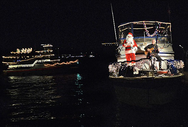 Santa Claus sings songs as Jim Palmour plays guitar during the Lighted Boat Parade on Friday at Ross's Landing.